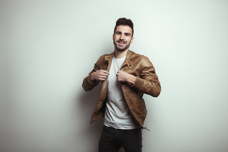 Happy young man with stubble wearing leather jacket and t-shirt, empty studio wall background, studio indoors