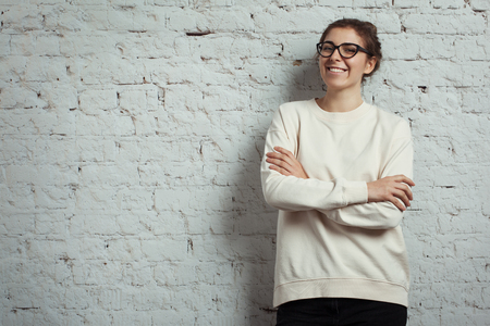 Handsome smiling woman hipster wearing blank sweater and eye glasses. White bricks wall background, studio indoors Stok Fotoğraf