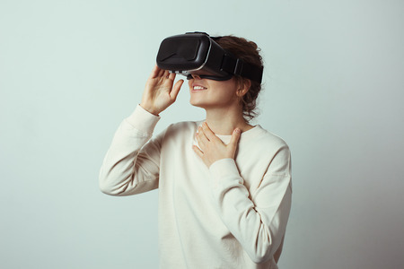 Young handsome woman wearing virtual headset. Excited Hipster using VR glasses. Empty studio wall background, studio indoors Stok Fotoğraf