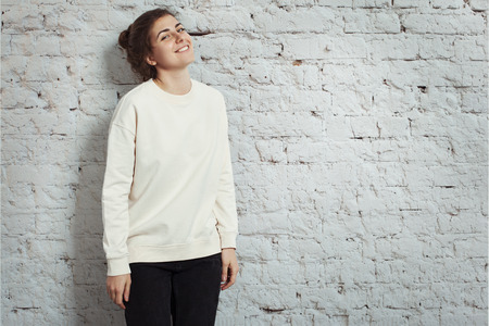 Portrait of cheerful woman hipster wearing blank sweater. White bricks wall background, studio indoors