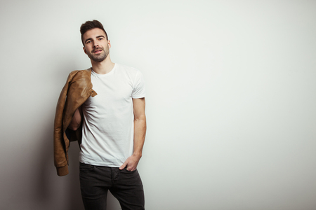 Young man with stubble in blank t-shirt and jacket, empty wall in studio background, studio indoors