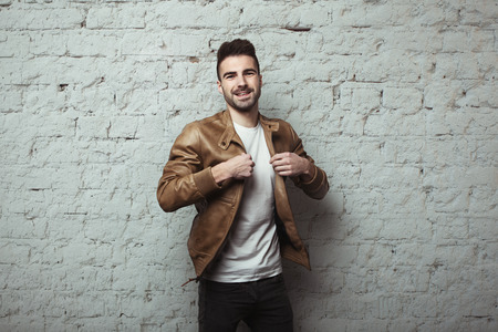 Happy young man with stubble wearing leather jacket and t-shirt, white bricks wall background, studio indoors