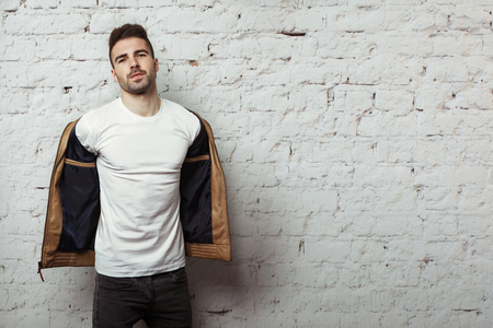 Handsome man in blank t-shirt taking off his leather jacket, white bricks wall background, studio indoors