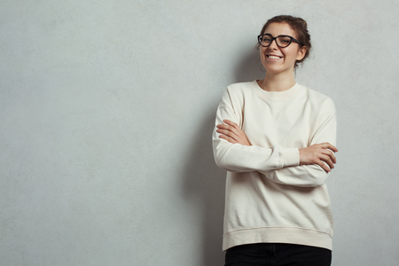 Handsome smiling woman hipster wearing blank sweater and eye glasses. Grey concrete wall background, studio indoors