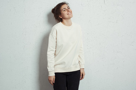 Portrait of cheerful woman hipster wearing blank sweater. Grunge wall with cracks background, studio indoors Stok Fotoğraf