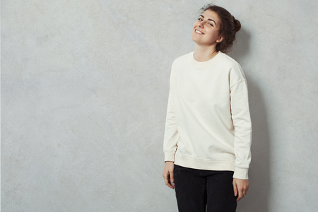 Portrait of cheerful woman hipster wearing blank sweater. Grey concrete wall background, studio indoors
