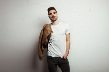 Young man with stubble in blank t-shirt and jacket, white grunge wall with cracks background, studio indoors