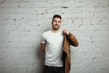Smiling man in blank t-shirt and jacket, white bricks wall background, studio indoors