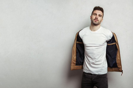 Handsome man in blank t-shirt taking off his leather jacket, grey concrete wall background, studio indoors Stok Fotoğraf