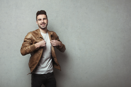 Happy young man with stubble wearing leather jacket and t-shirt, grey concrete wall background, studio indoors