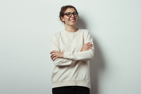 Handsome smiling woman hipster wearing blank sweater and eye glasses. Empty studio wall background, studio indoors