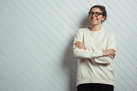 Handsome smiling woman hipster wearing blank sweater and eye glasses. White wooden wall background, studio indoors