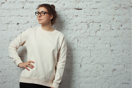 Portrait of charming woman hipster wearing blank sweater and eye glasses. White bricks wall background, studio indoors