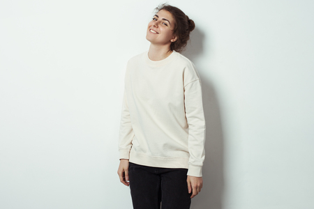 Portrait of cheerful woman hipster wearing blank sweater. Empty studio wall background, studio indoors