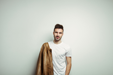 Smiling man in blank t-shirt wearing leather jacket on the shoulder, white empty studio wall background, studio indoors