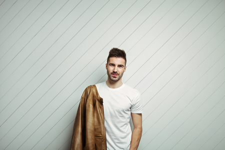 Smiling man in blank t-shirt wearing leather jacket on the shoulder, white wooden background, studio indoors Stok Fotoğraf
