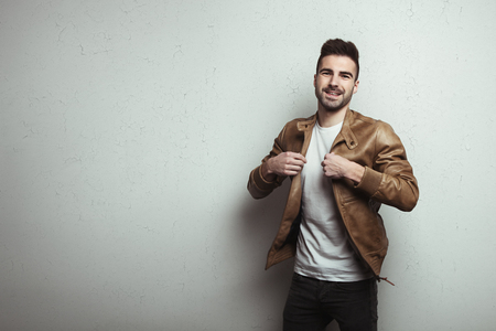 Happy young man with stubble wearing leather jacket and t-shirt, white grunge wall with cracks background, studio indoors