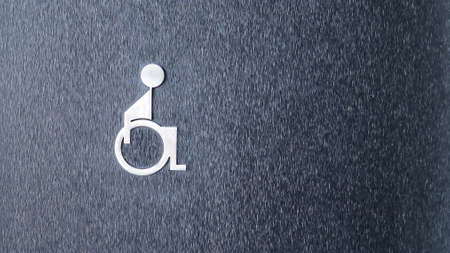 The symbol of the disabled toilet on the black wall.
