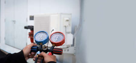 Air repair mechanic using measuring equipment for filling industrial factory air conditioners.