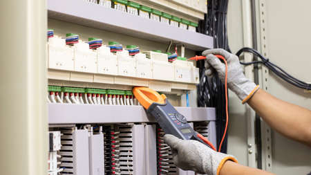 Electrical engineer tests the operation of the electric control cabinet on a regular basis for maintenance.