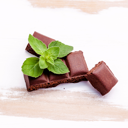 pieces of chocolate with mint on white wooden background Banco de Imagens - 64393997