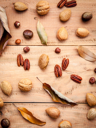 nutshell: Various kinds of nutshell  walnuts kernels ,hazelnuts, almond kernels and pecan with dried leaves set up on rustic wooden background. Stock Photo