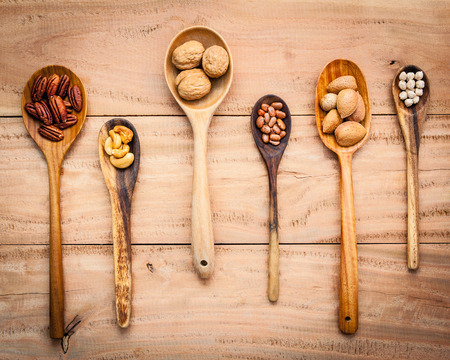 nutshell: Various kinds of nutshell  walnuts kernels ,hazelnuts, cashew nut, almond kernels and pecan in wooden spoons up on rustic wooden background. Stock Photo