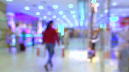 acquirer: Blurred woman in red walking in a modern shop