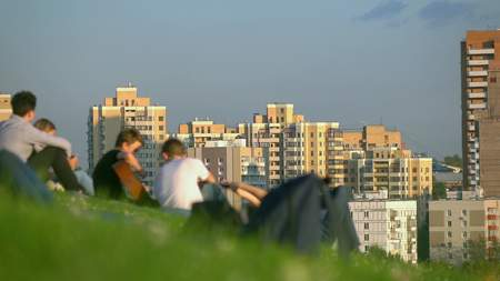 Unrecognizable teenagers hanging out in city park and listening to guitar against cityscape Stock Photo