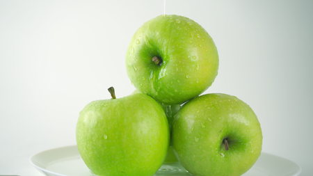 Water being poured over green apples, light grey background