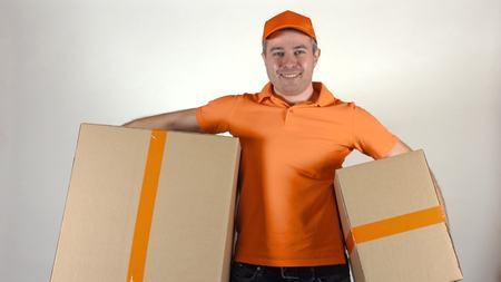 carreer: Delivery guy in orange uniform giving parcels Stock Photo