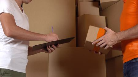 carreer: Store assistant in orange uniform giving a box to a customer. Cartons background