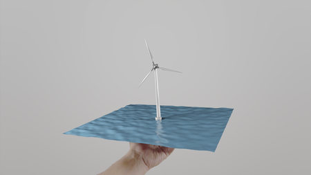 ecologic: Man twists in hand a windmill located on water. Gray background. Alternative ecologic power generation