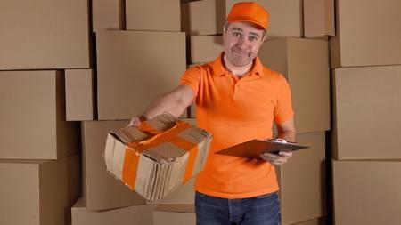 unprofessional: Man in orange uniform delivering heavily damaged parcel to customer. Brown cartons background. Unprofessional work concept Stock Photo