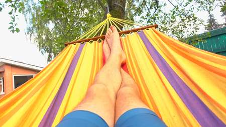 shoeless: Man having rest in bright hammock Stock Photo