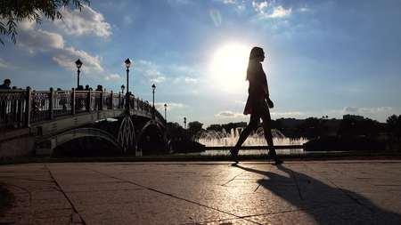 Silhouette of a slim girl in high heels walking on sunny park embankment
