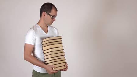 strangeness: Nerdy man in black rim glasses carrying big stack of books Stock Photo