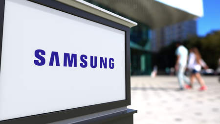 logo samsung: Street signage board with Samsung logo. Blurred office center and walking people background. Editorial 3D rendering United States