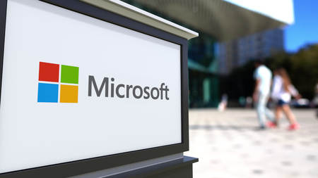 Street signage board with Microsoft logo. Blurred office center and walking people background. Editorial 3D rendering United States