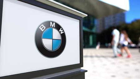 trustworthy: Street signage board with BMW logo. Blurred office center and walking people background. Editorial 3D rendering United States