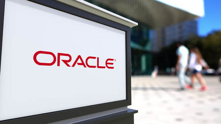 oracle: Street signage board with Oracle Corporation logo. Blurred office center and walking people background. Editorial 3D rendering United States