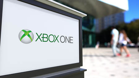 xbox: Street signage board with Xbox One logo. Blurred office center and walking people background. Editorial 3D rendering United States