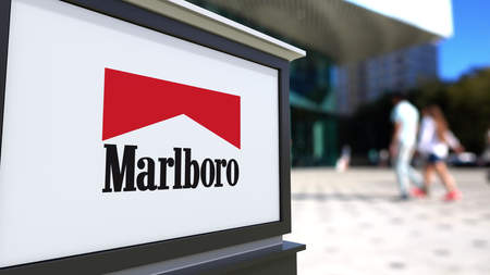 Street signage board with Marlboro logo. Blurred office center and walking people background. Editorial 3D rendering United States