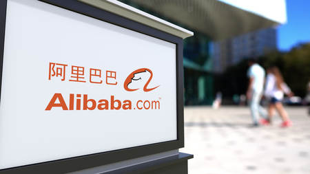 Street signage board with Alibaba.com logo. Blurred office center and walking people background. Editorial 3D rendering United States