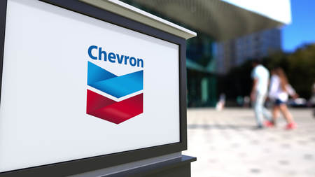 Street signage board with Chevron Corporation logo. Blurred office center and walking people background. Editorial 3D rendering United States 에디토리얼