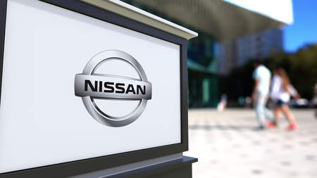 nissan: Street signage board with Nissan logo. Blurred office center and walking people background. Editorial 3D rendering United States Editorial