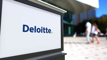 lawer: Street signage board with Deloitte logo. Blurred office center and walking people background. Editorial 3D rendering United States