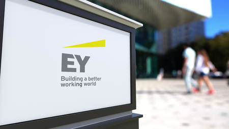 lawer: Street signage board with Ernst & Young logo. Blurred office center and walking people background. Editorial 3D rendering United States