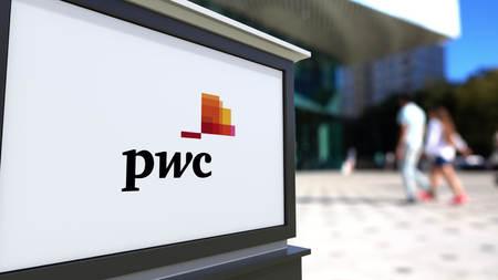 PricewaterhouseCoopers PwC 로고가있는 거리 표지판. 흐리게 office 센터와 걷는 사람들이 배경. Editorial 3D rendering 미국
