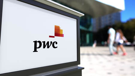Street signage board with PricewaterhouseCoopers PwC logo. Blurred office center and walking people background. Editorial 3D rendering United States